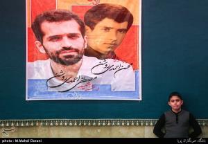 علیرضا احمدی روشن در کنار پوستر پدر
