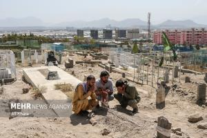 عکس/ سوگواری بر مزار یکی از 7 کودک افغان که بر اثر حمله آمریکا کشته شد
