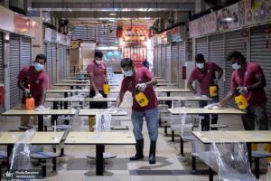 کارگران در حال ضدعفونی کردن یک مرکز فروش و بازار در سنگاپور