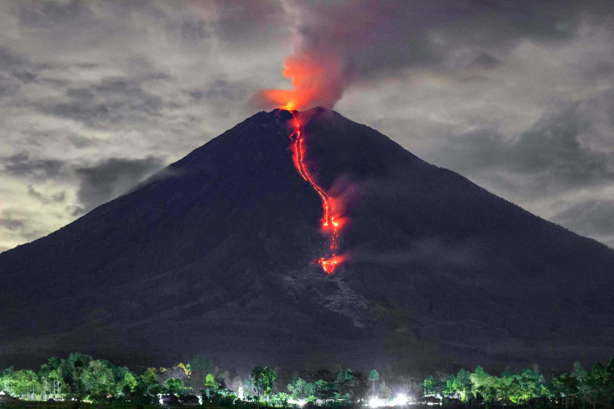 تصویری خاص از جاری شدن گدازه های سرخ رنگ کوه آتشفشانی