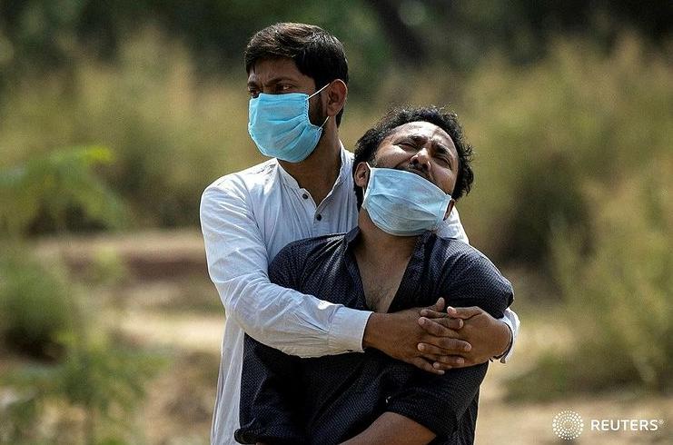 تصویری دردناک از بی تابی مرد هندی با جسد پدر که بر اثر کرونا درگذشته