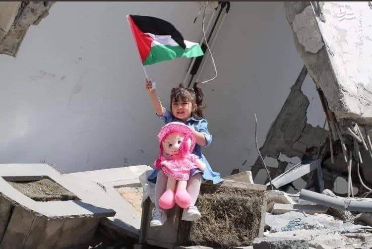 تصویری متاثر کننده از کودک غزه ای به همراه پرچم کشورش در میان خرابهها
