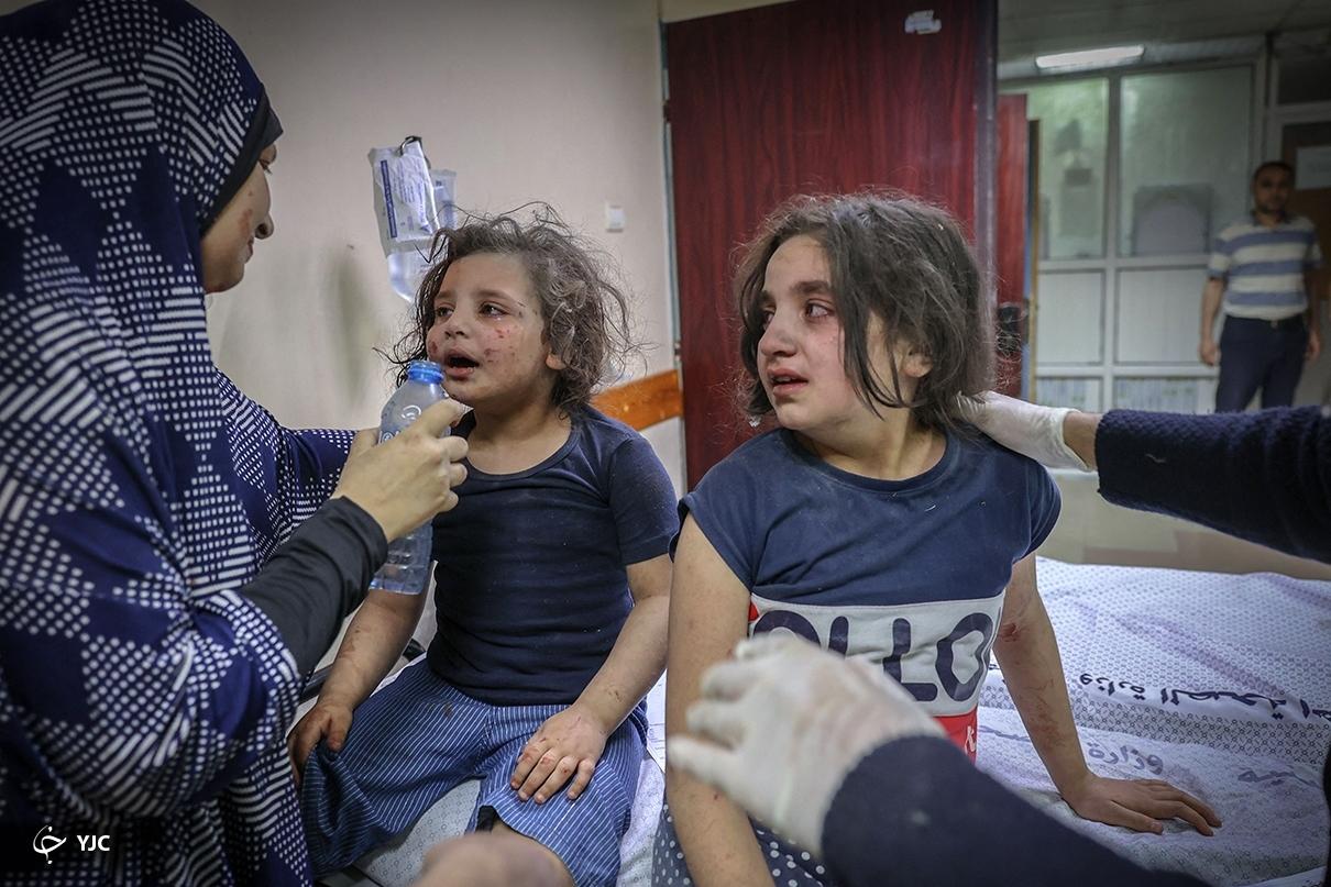 عکس/ تلاش برای آرام کردن کودکان در میان بمباران