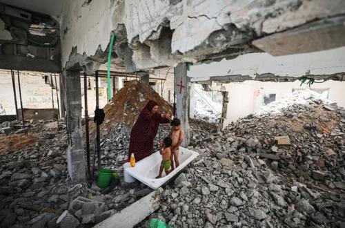 مادر فلسطینی در حال شستشوی فرزندان در خانه ویران شده