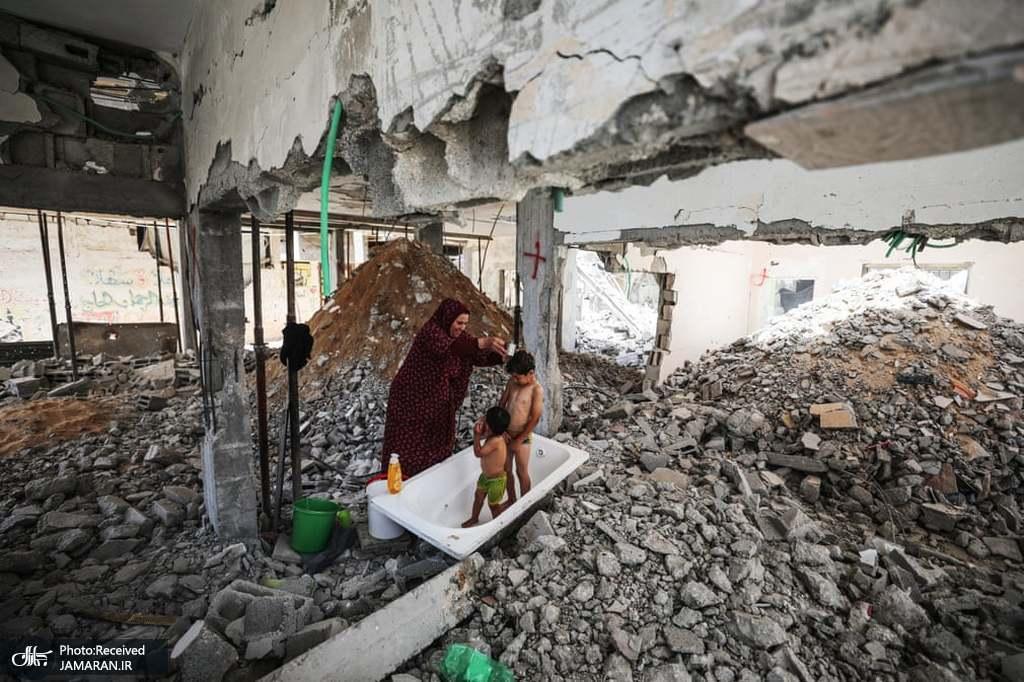 حمام کردن دو کودک فلسطینی در میان آوارها