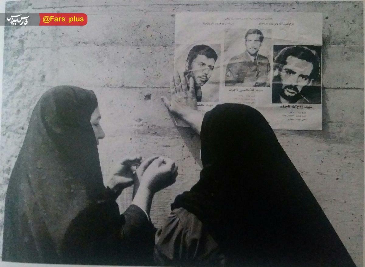 عکس/ مادری در حال نصب اعلامیه سه فرزند شهیدش