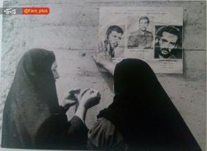 عکس/ مادري در حال نصب اعلاميه سه فرزند شهيدش