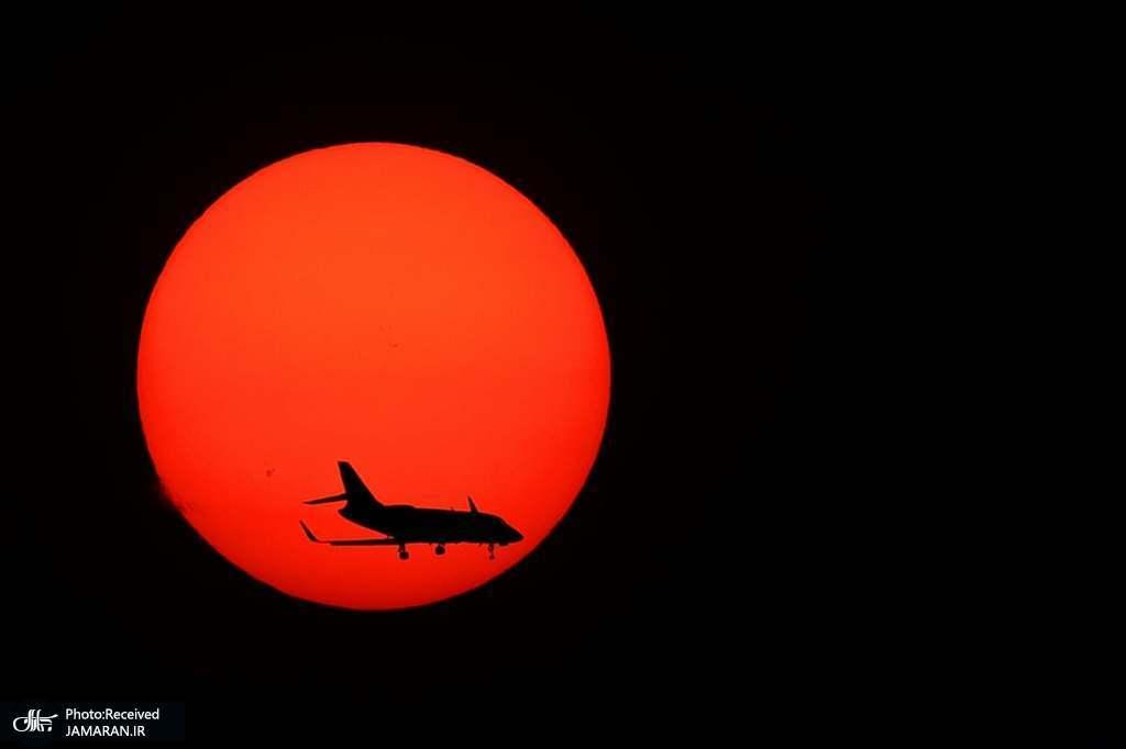 عبور هواپیما از مقابل غروب آفتاب در کالیفرنیا