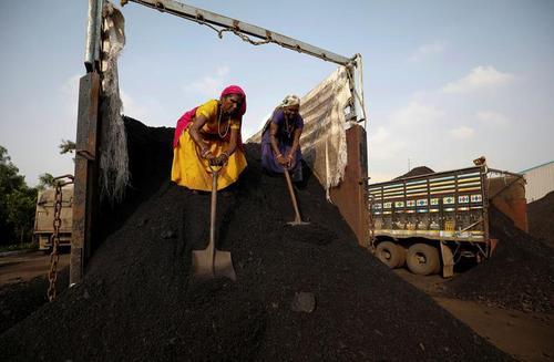 زنان هندیِ کارگر در حال تخلیه بار زغال یک کامیون