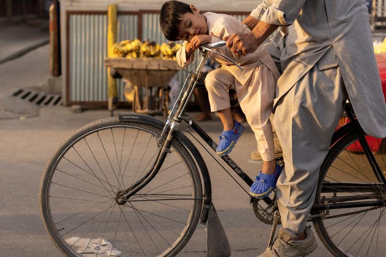 تصویری جالب از خواب پسربچه افغان روی دوچرخه